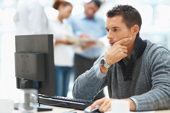 Young professional using a computer with colleagues at the back
